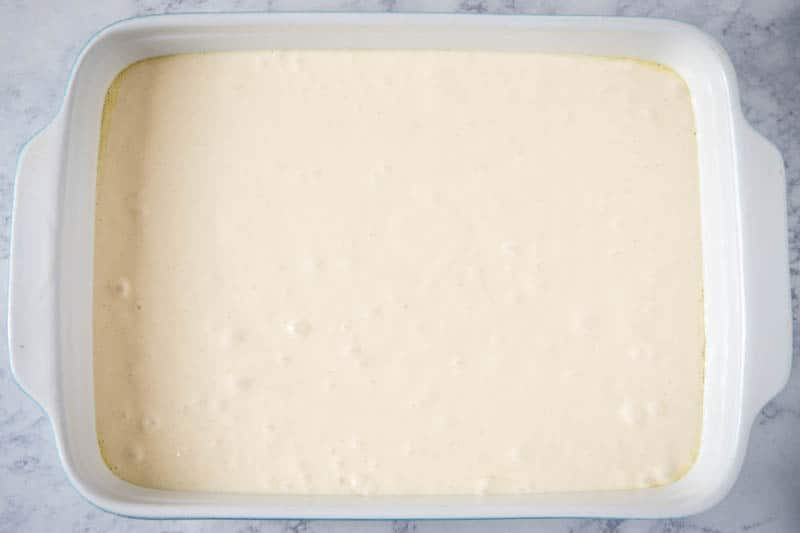 white cake batter in 9x13 baking dish on white marble countertop