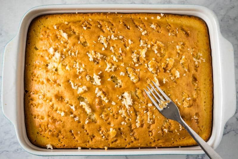 poking poke cake with fork in 9x13 baking dish