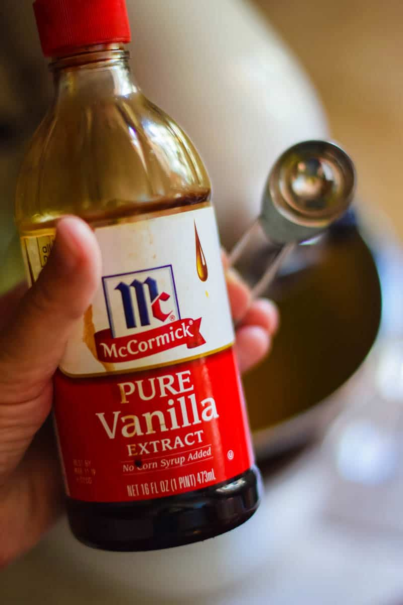 hand holding bottle of McCormick Pure Vanilla Extract with teaspoon