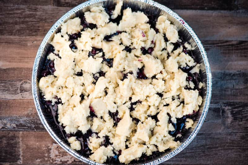 sugar cookie topping crumbled over blueberry pie filling in round foil pan