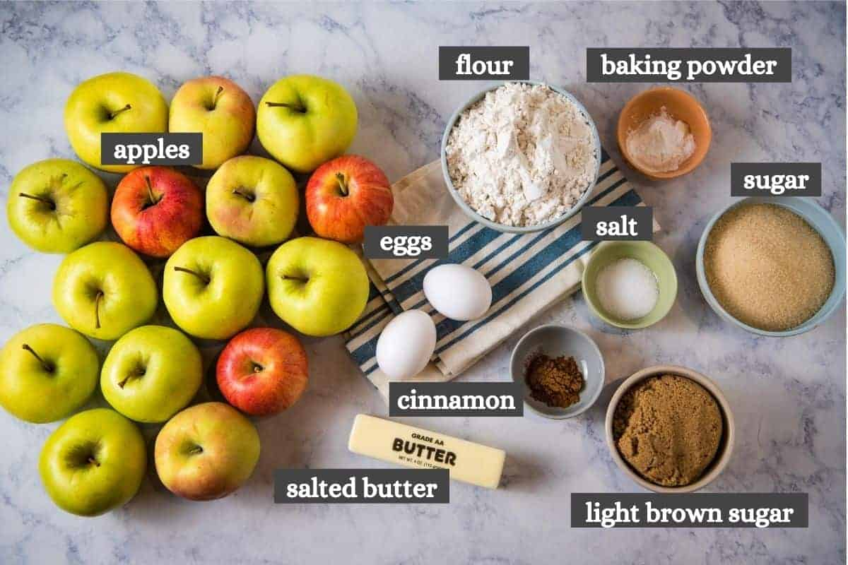 ingredients for making apple crumble recipe on white marble countertop