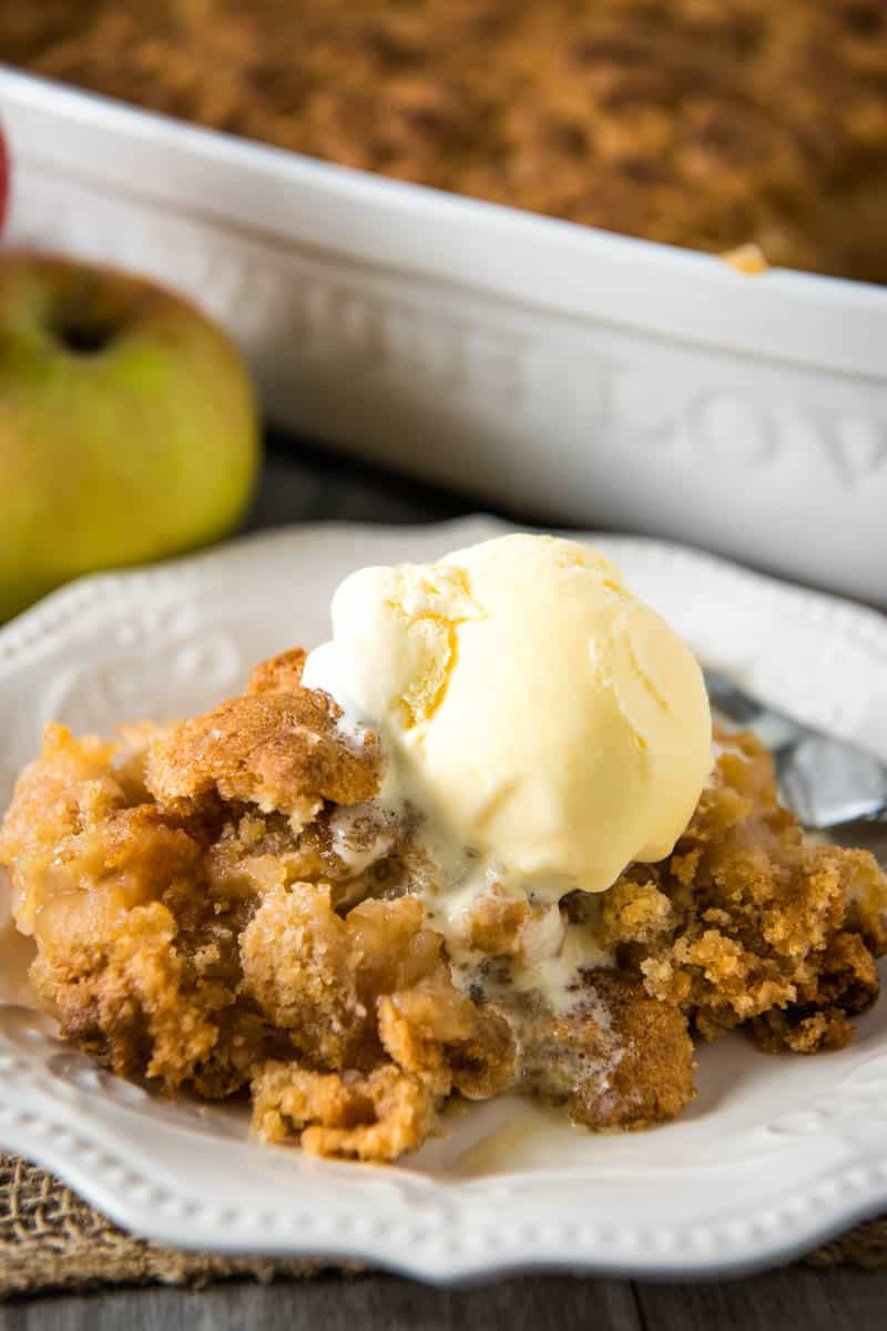 serving of apple crumble without oats, with scoop of vanilla ice cream on white plate with fork