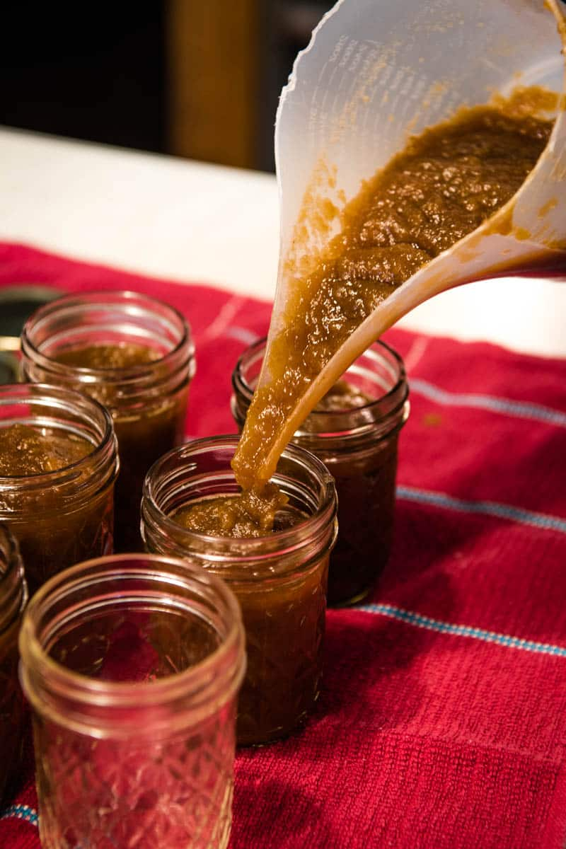 pouring CrockPot apple butter into 8-ounce jelly jars for canning