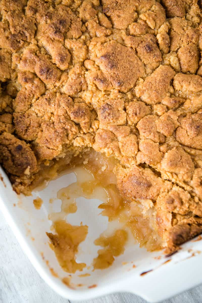 classic apple crumble baked and scooped in white casserole dish