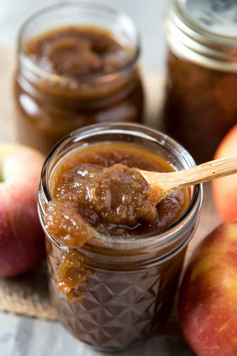 Crock Pot apple butter in a jar with small wooden spoon