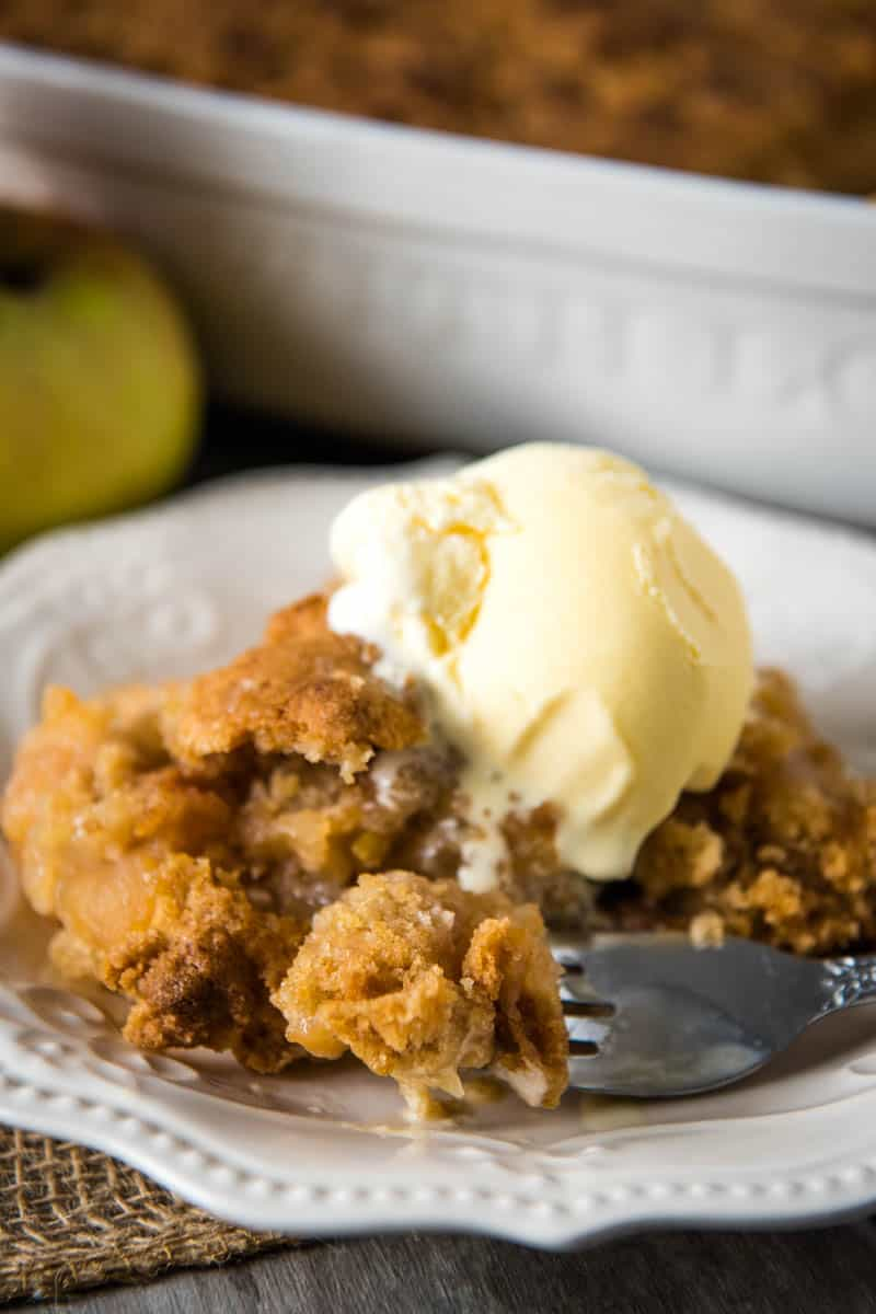 fork with bite of easy apple crisp, topped with scoop of vanilla ice cream, on white plate