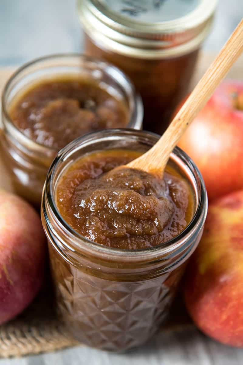 slow cooker apple butter in jelly jar with small wooden spoon