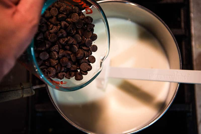 adding chocolate chips to milk in saucepan to make hot chocolate from chocolate chips