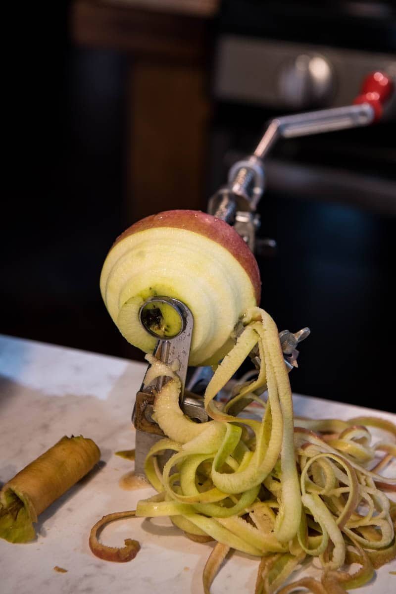 apple peeler for apple butter peeling, coring, and slicing apple on white countertop
