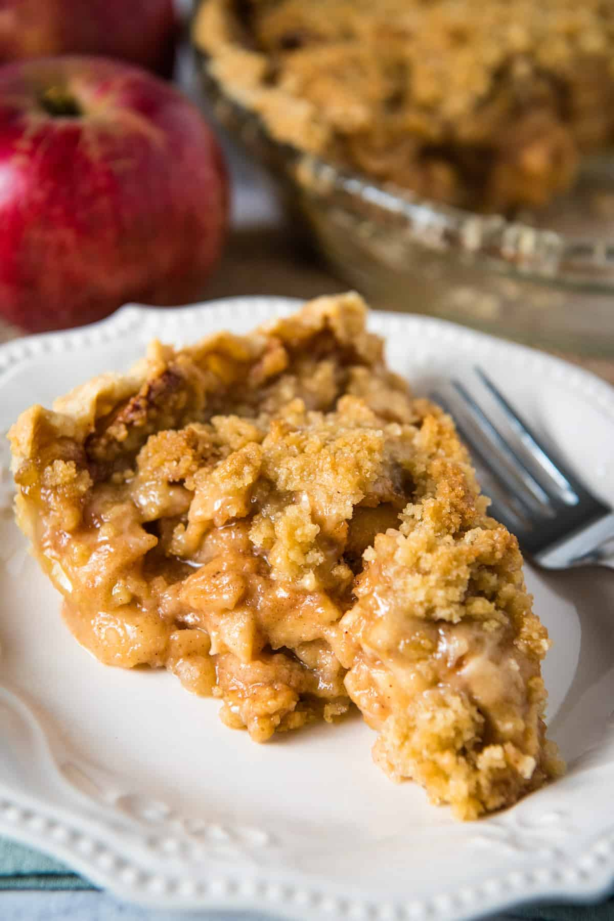 slice of apple pie with streusel topping on white plate with fork
