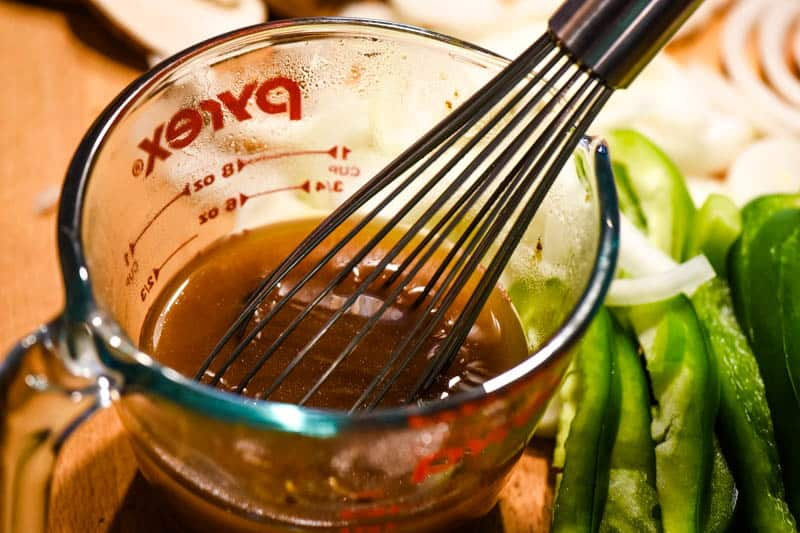 whisking beef broth with flour in glass Pyrex measuring cup