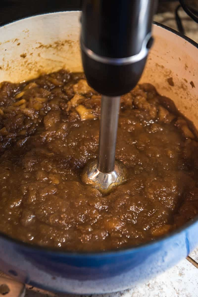 blending stovetop cinnamon apple butter in blue Dutch oven with immersion blender