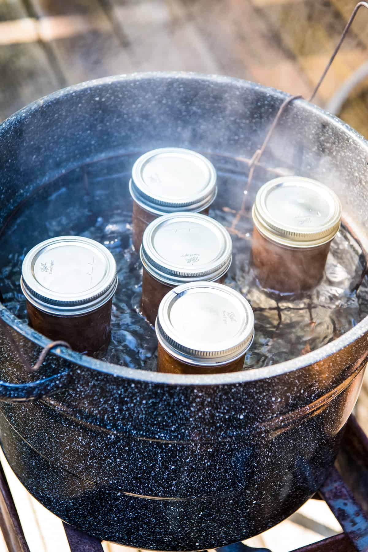 hot water bath canning jars of apple butter in water bath canner