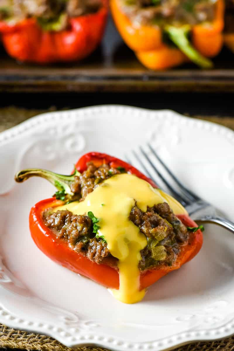 cheesesteak stuffed pepper with Cheez Whiz on top, on white plate with fork