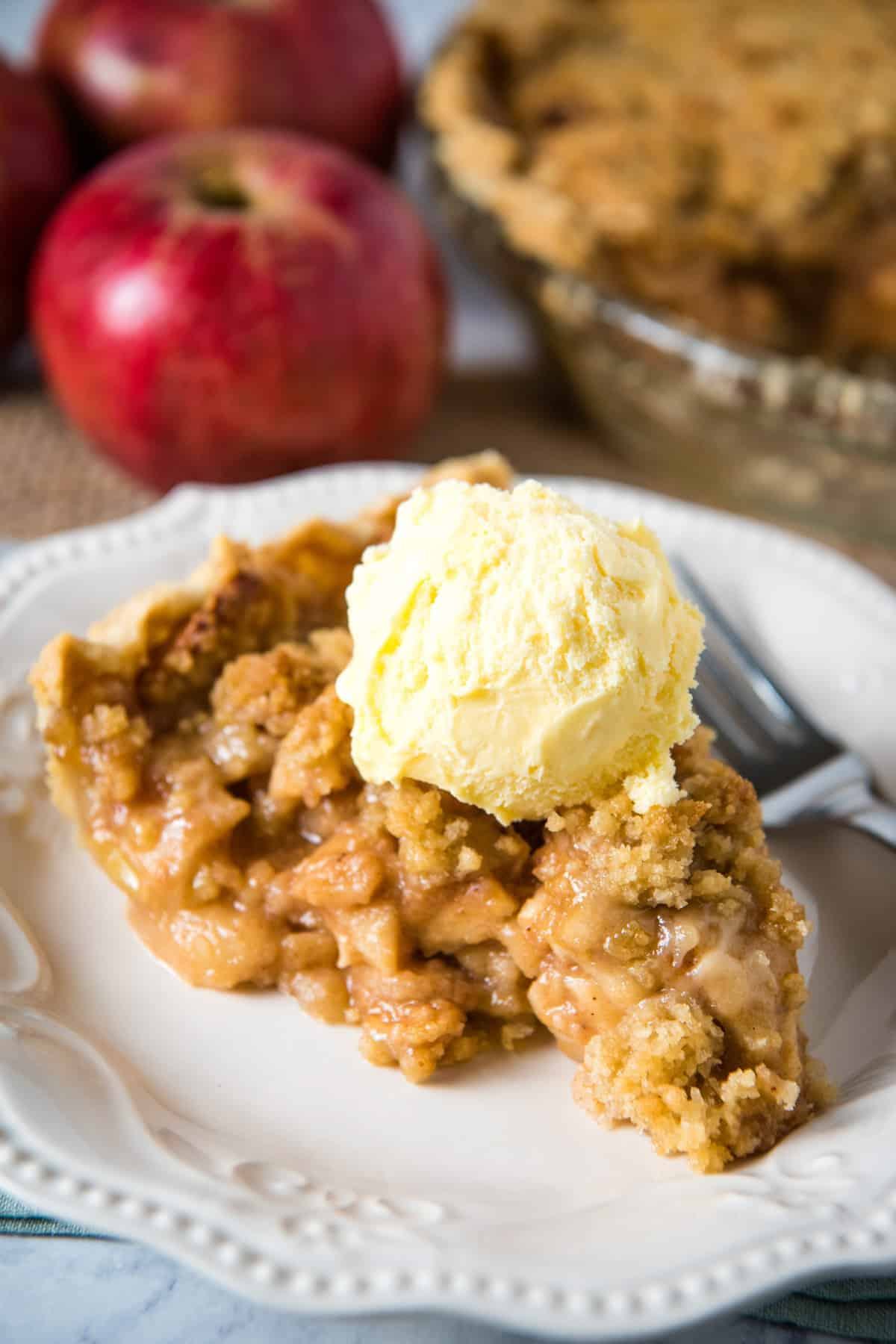 slice of Dutch apple crumb pie with scoop of vanilla ice cream on top, on white plate with fork