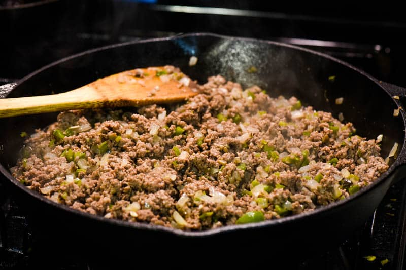ground beef with peppers and onions and mushrooms, cooking in cast iron skillet with wooden spatula for stirring