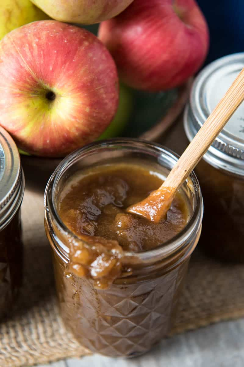 canned apple butter in jelly jar with small wooden spoon