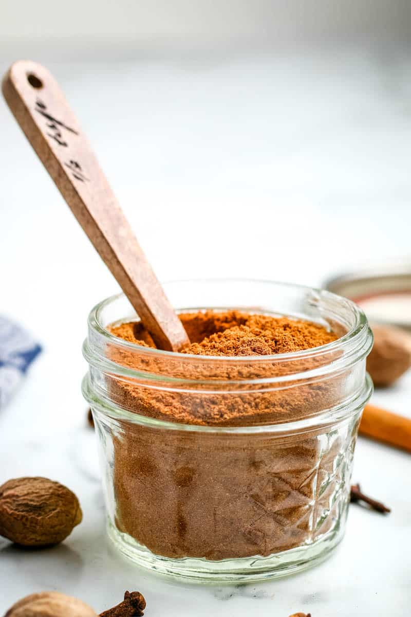 small mason jar with homemade pumpkin pie spice and small wooden spoon
