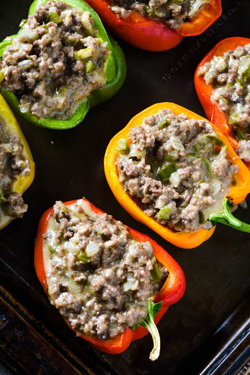 spooned ground beef mixture into Philly cheesesteak stuffed peppers on baking sheet