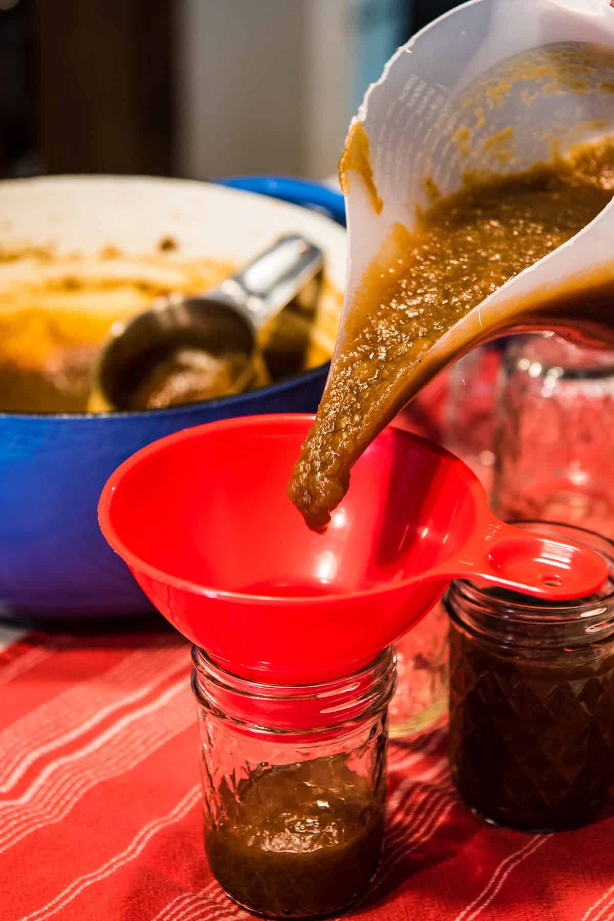 pouring easy stovetop apple butter from funnel pitcher into jelly jar using red jar funnel and funnel pitcher
