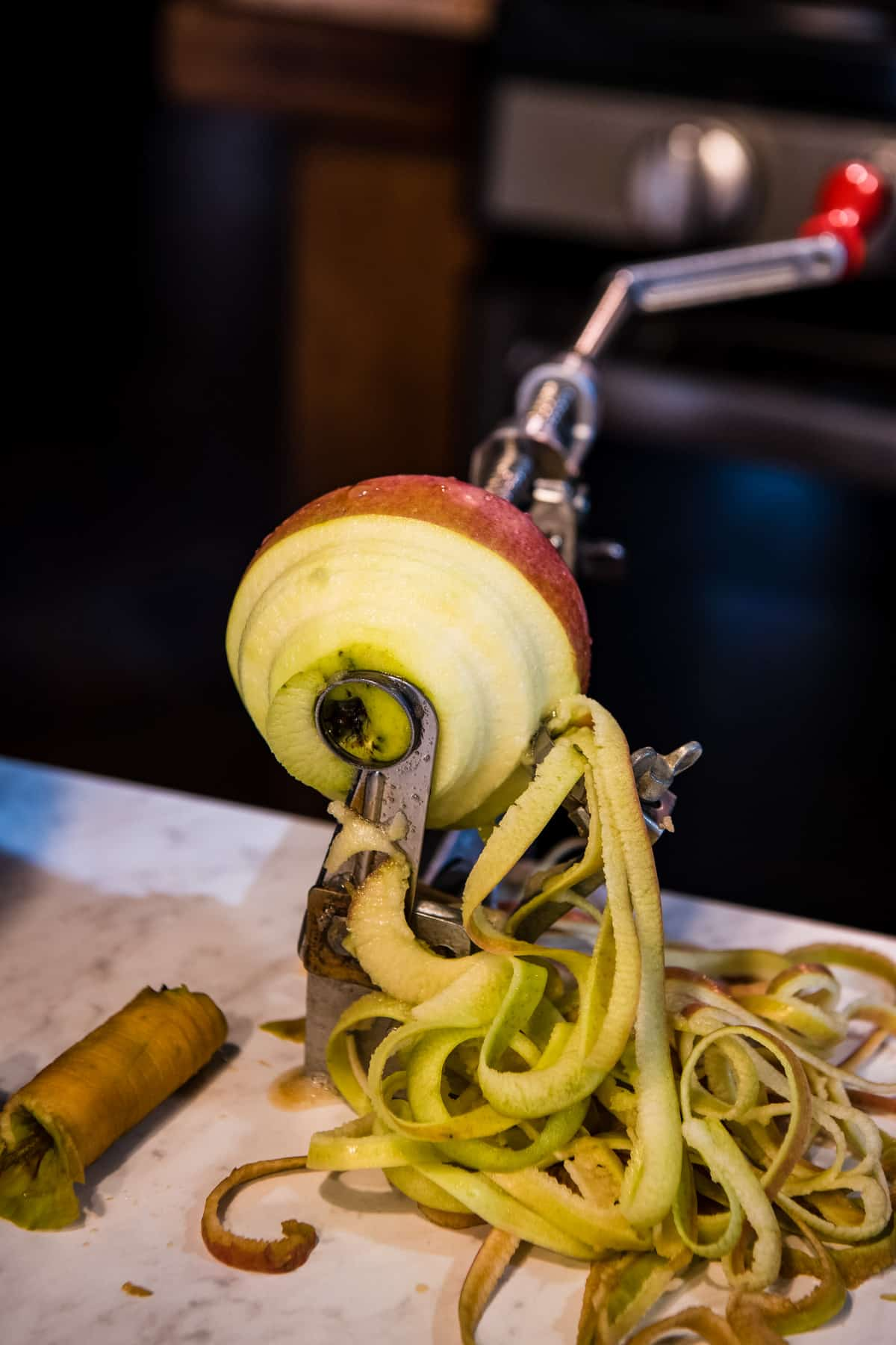 Johnny apple peeler for peeling, coring, and slicing apples on white countertop