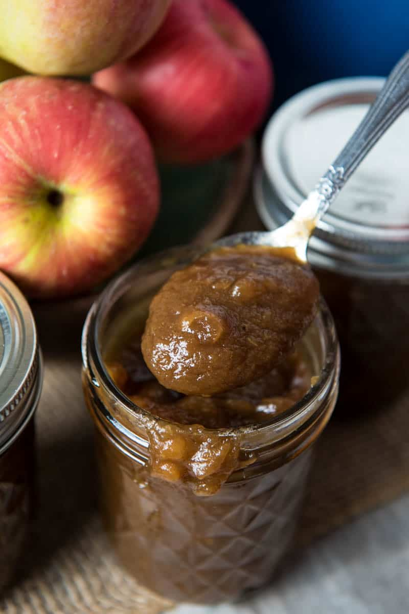 spoonful of old-fashioned apple butter over jelly jar with drips of apple butter on rim