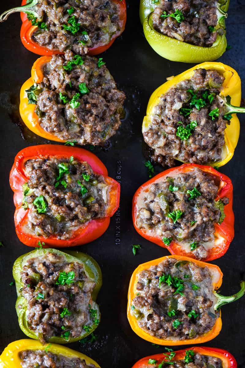 baked Philly cheese stuffed peppers, sprinkled with parsley, on baking sheet