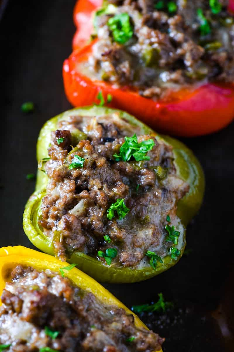 Philly cheesesteak stuffed bell peppers, including green stuffed pepper, on baking sheet