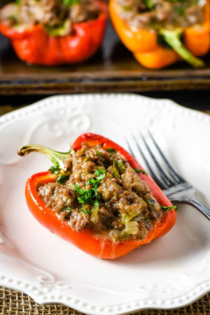 red Philly cheesesteak stuffed pepper with ground beef, sprinkled with parsley, on white plate with fork