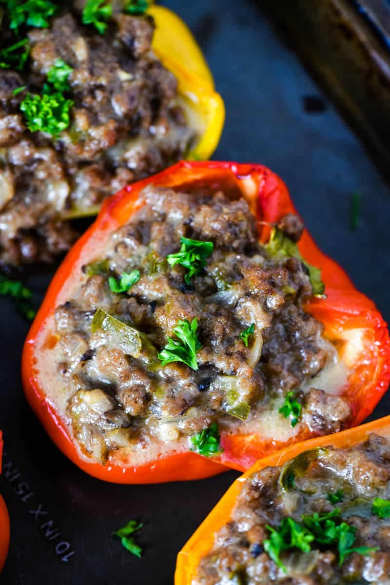 colorful Philly cheesesteak stuffed peppers ground beef style, sprinkled with parsley, on baking sheet