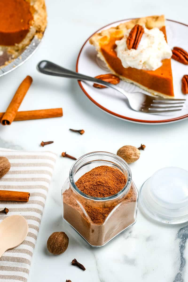 Pumpkin pie spice blend in small glass jar on white marble countertop and slice of pumpkin pie on red rimmed white plate with fork