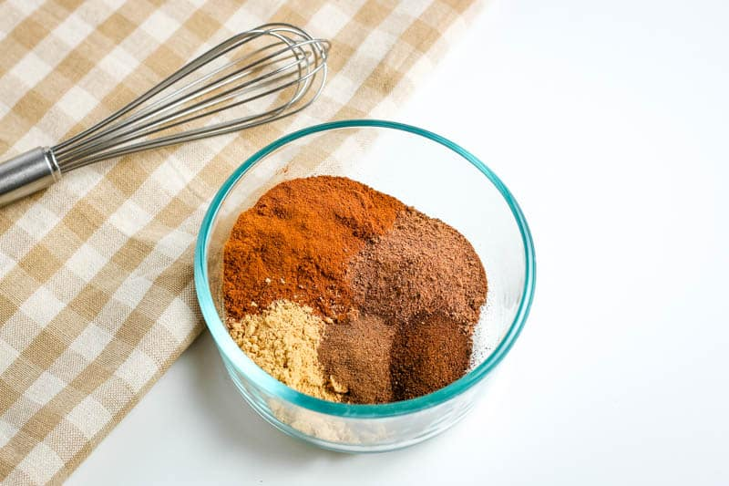 small glass bowl of pumpkin pie spice ingredients with whisk