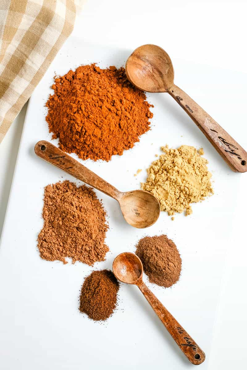 spices and seasonings used to make pumpkin spice seasoning, on white countertop with small wooden spoons and tan checkered gingham towel