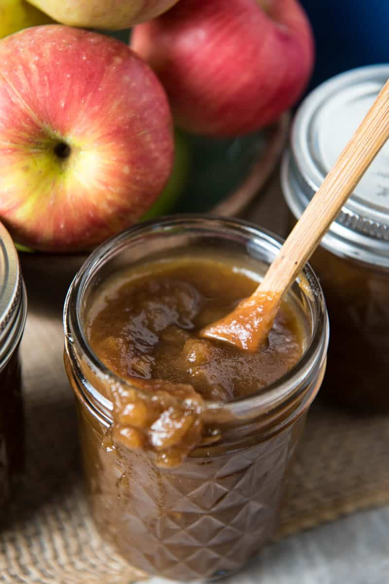 stovetop apple butter in 8 ounce jelly jar with tiny wooden spoon