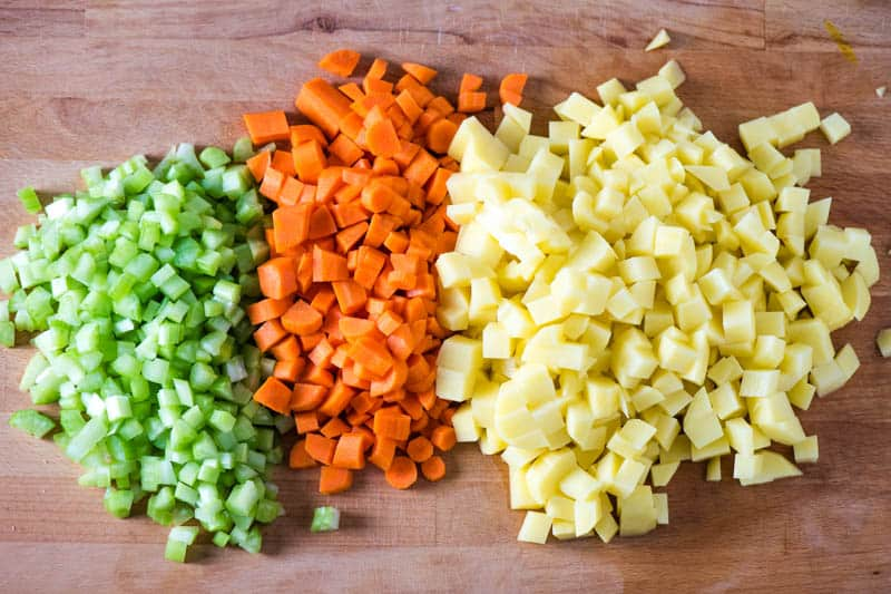 chopped fresh celery, carrots, and potatoes for hearty vegetable soup on wooden cutting board