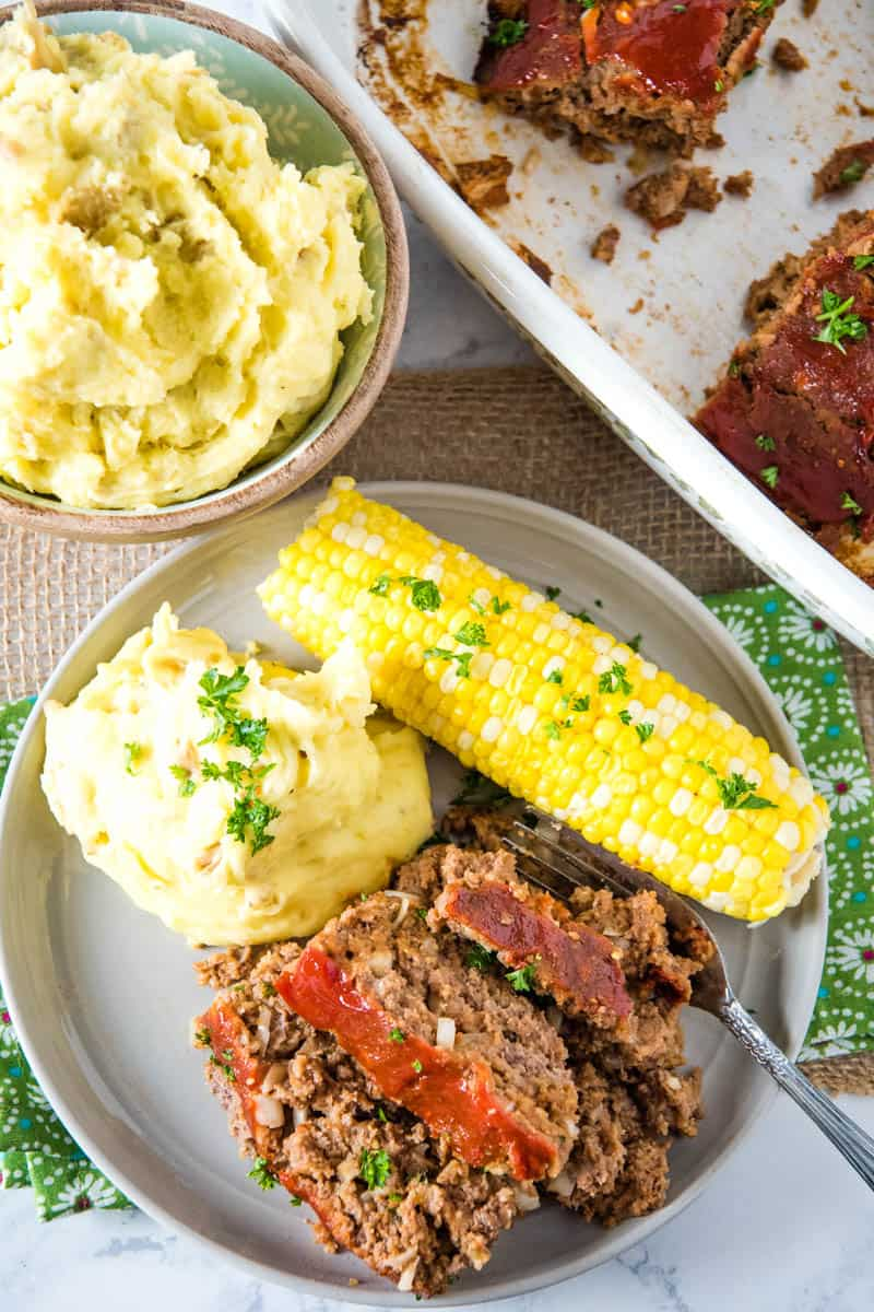 above gray plate of classic meatloaf with mashed potatoes and corn on the cob, with fork, on green and white flowered linen and tan burlap