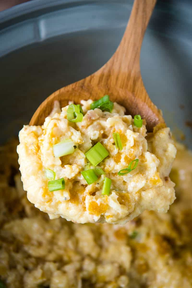 wooden spoonful of CrockPot funeral potatoes hash brown casserole, sprinkled with green onions, over gray slow cooker side dish