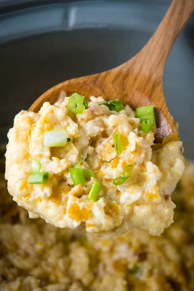 wooden spoonful of CrockPot funeral potatoes with green onions over gray slow cooker with casserole