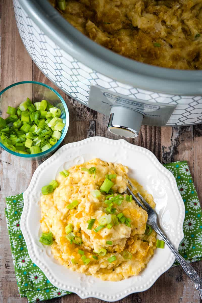 white plate full of CrockPot hash brown casserole with fork, with gray slow cooker and small bowl of green onions