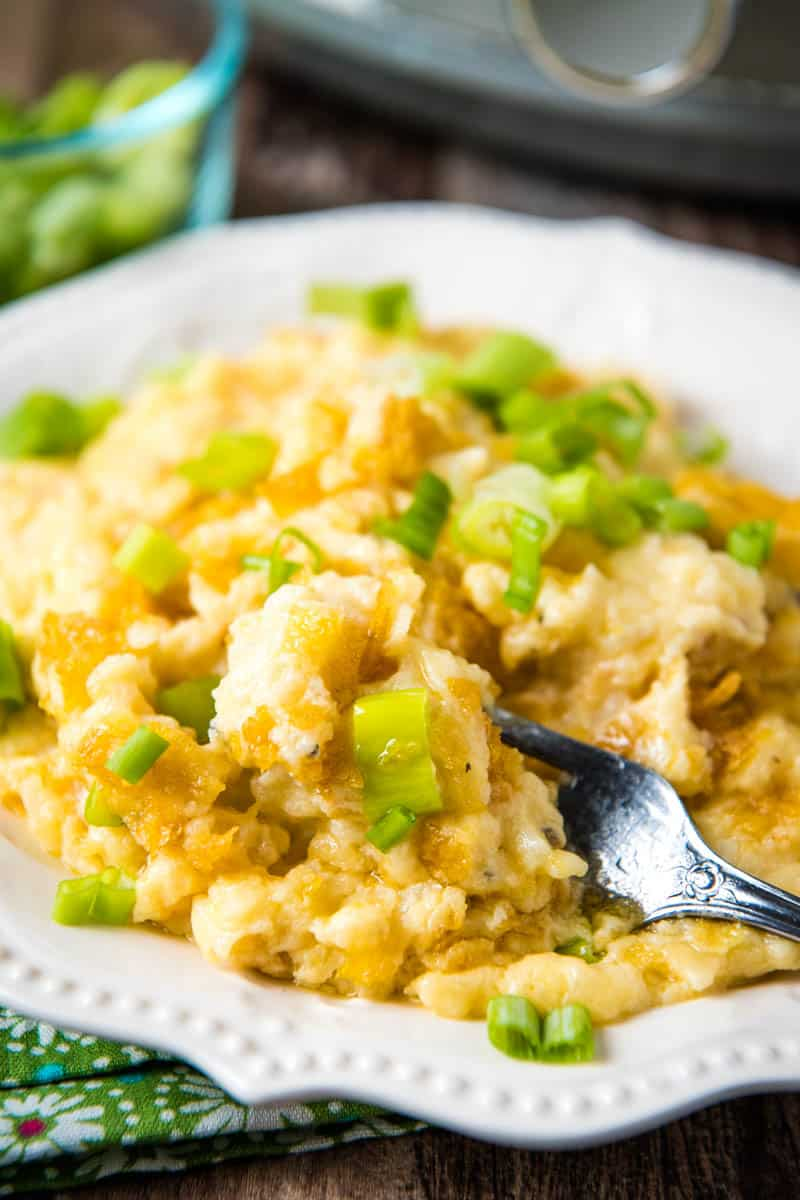 serving of CrockPot hashbrown casserole, sprinkled with green onions, on white plate with fork