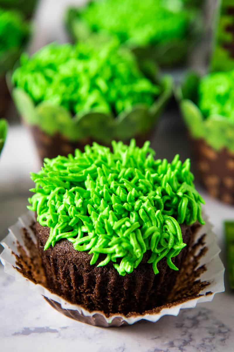 chocolate cupcake with green grass buttercream frosting, with white liner pulled away from cupcake