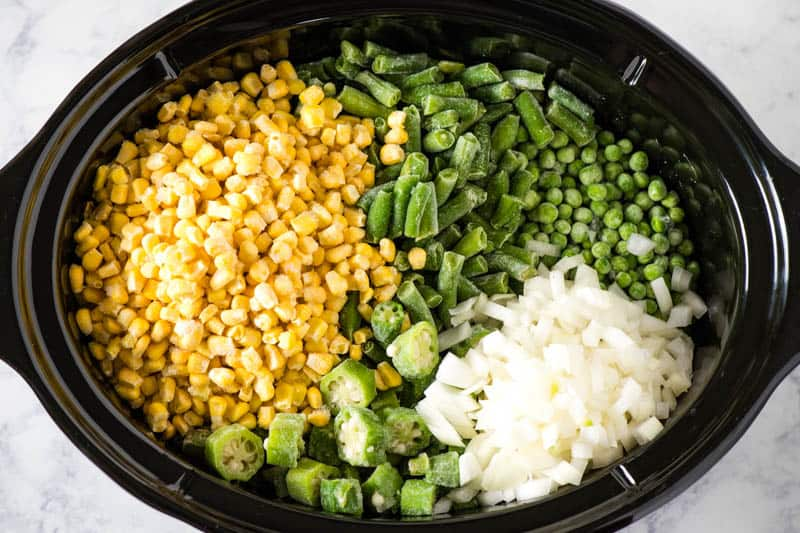 frozen corn, green beans, peas, okra, and onion in black slow cooker