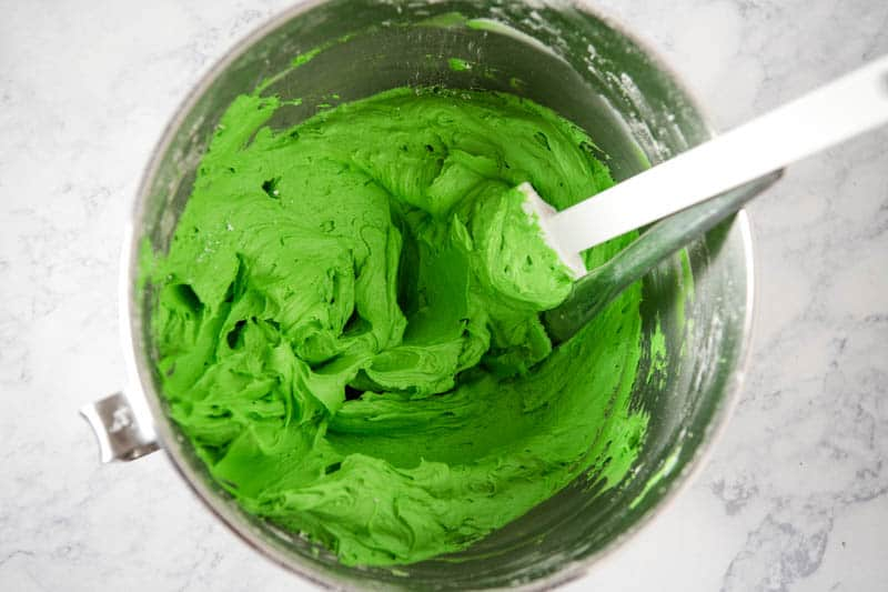green buttercream frosting in KitchenAid mixing bowl on white marble countertop