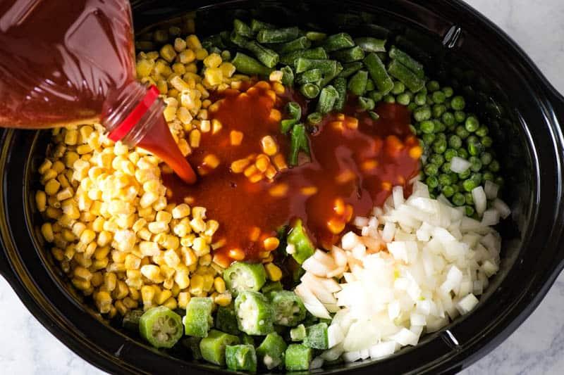 pouring V8 juice into black slow cooker while making CrockPot V8 vegetable soup
