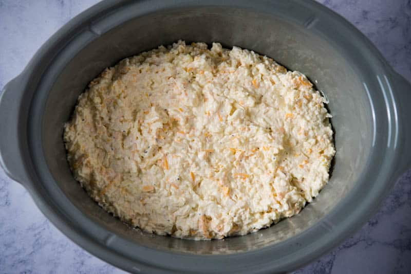 mixture for slow cooker hash brown casserole spread in gray slow cooker