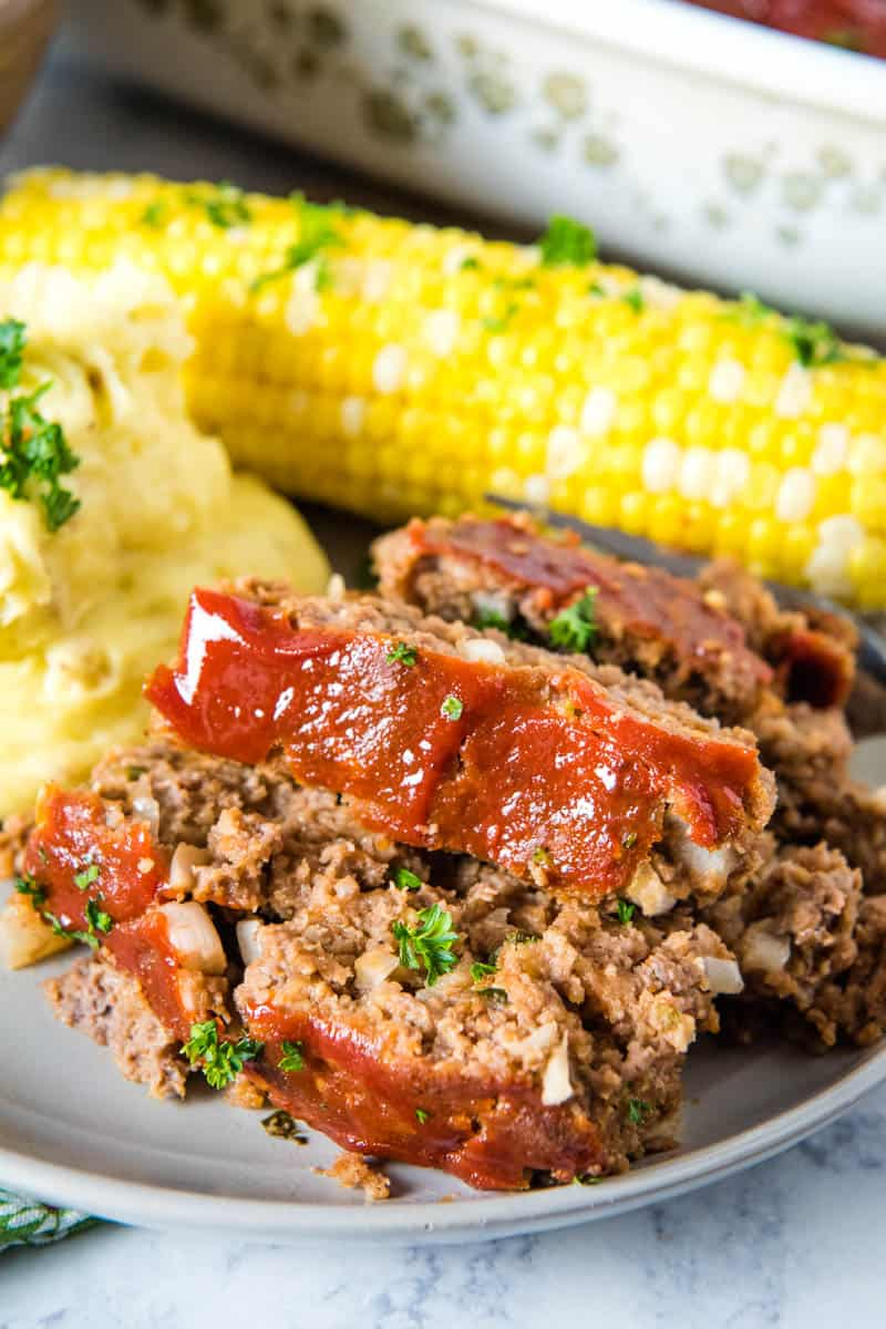 slices of traditional meatloaf with meatloaf sauce topping on gray plate