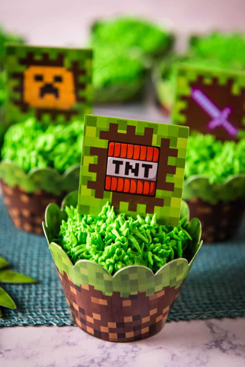 Minecraft cupcakes with Minecraft cupcake wrappers and Minecraft TNT cupcake topper on white marble countertop with blue burlap