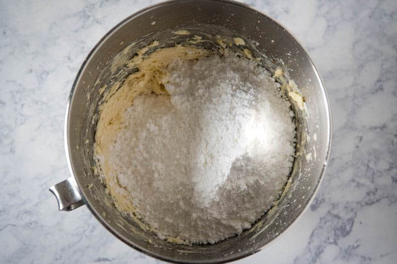 mixing powdered sugar into buttercream frosting in KitchenAid mixing bowl on white marble countertop
