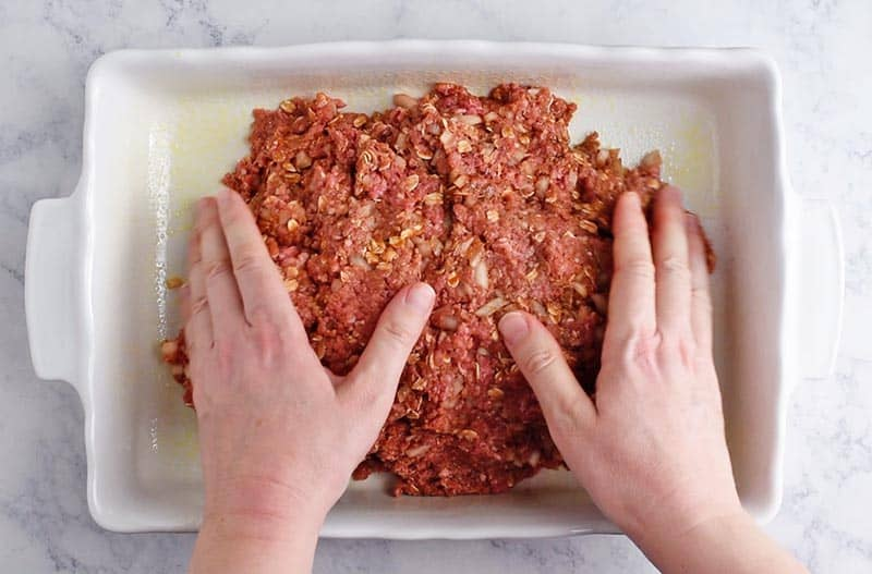 hands shaping oatmeal meatloaf in white baking dish on white marble countertop