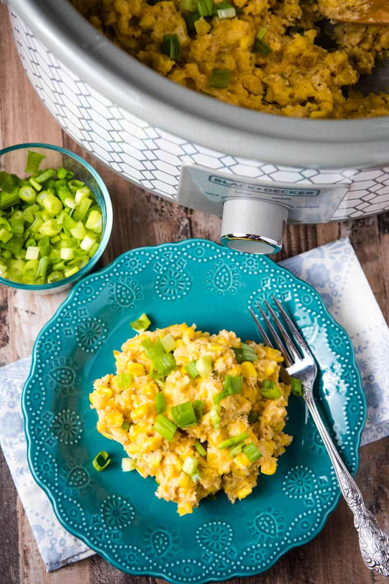 slow cooker corn pudding in slow cooker and on teal plate with fork, on wooden countertop